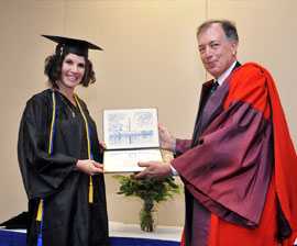 Student Christiana Remick accepting her Bachelor of Science Degree from Humane Society University president Andrew Rowan