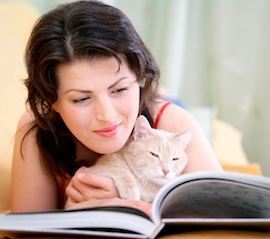 Woman reading a book with a cat