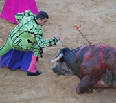 A matador prepares to knife the bull as it lies on the ground bleeding.
